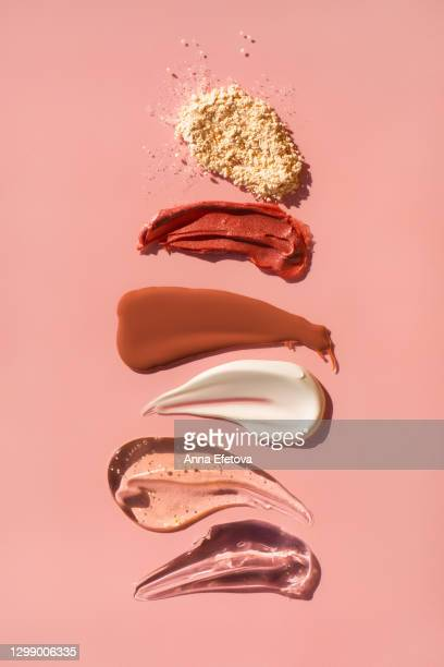 row of smears of assorted cosmetic products and face powder on pink background. trendy selfcare products of the year - 舞台化粧 ストックフォトと画像