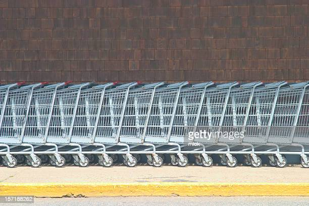 A row of stacked shopping carts in front of a brick wall