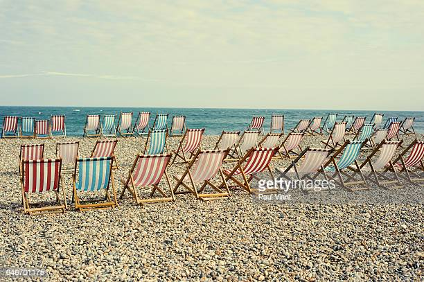 row of striped deckchairs on pebble beach