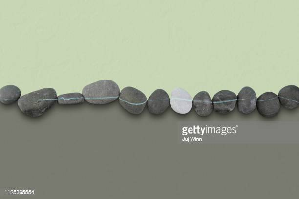Row of striped rocks on a color blocked background.