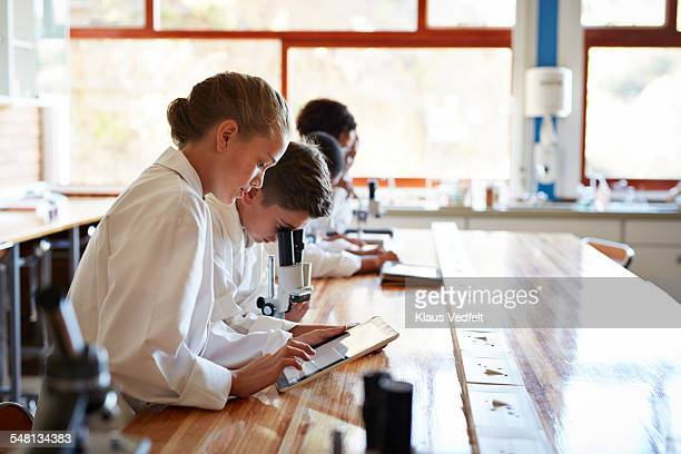 Row of students using tablet & microscope