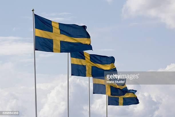 Row of Swedish flag poles against cloudy sky