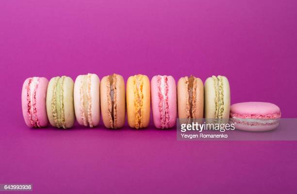 Row of sweet colorful French macaroons or macaron biscuits on purple background