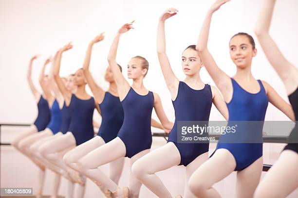 row of teenage ballerinas with arms outstretched - little girls in tights stock photos and pictures