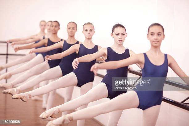 Row of teenage ballerinas with legs outstretched