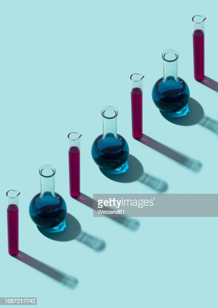 row of test tubes with liquid, cyan background - test tube stock pictures, royalty-free photos & images
