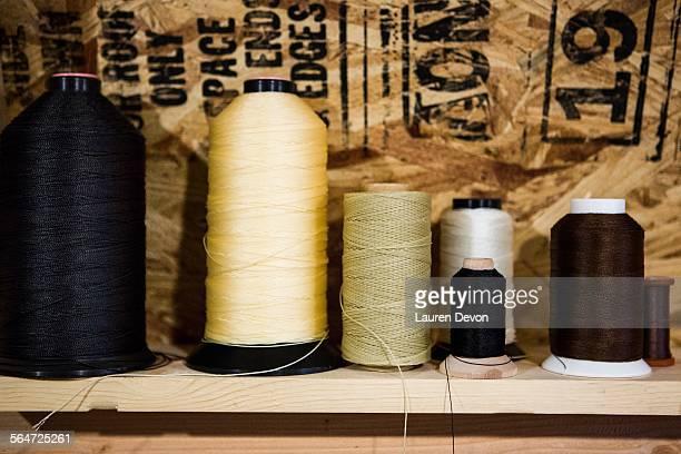 Row of thread bobbins on workshop shelf