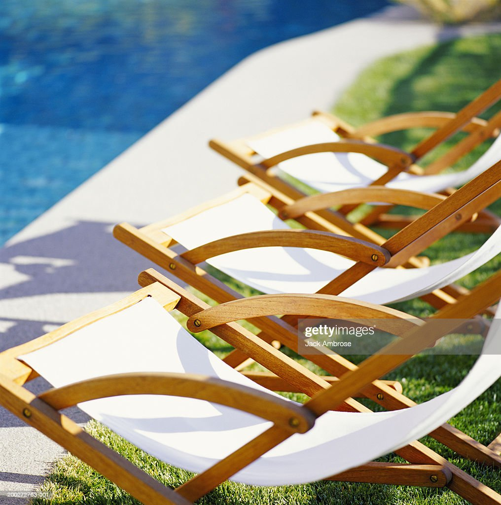 Row Of Three Empty Deck Chairs By Swimming Pool Stock-Foto ...