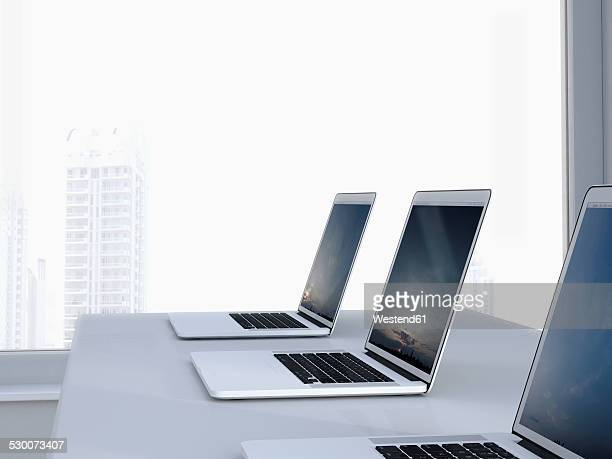 row of three laptops in an office, 3d rendering - small group of objects stock pictures, royalty-free photos & images