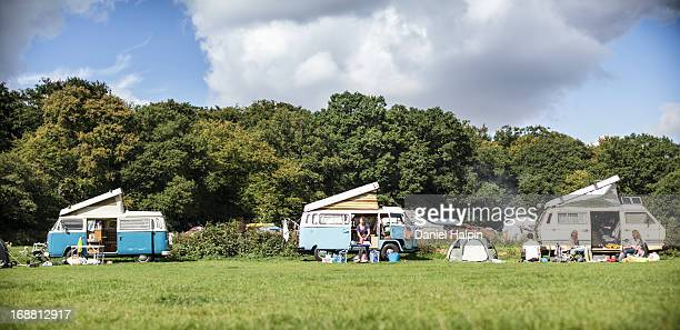 CONTENT] A row of three retro camper vans lined up in a field on a campsite