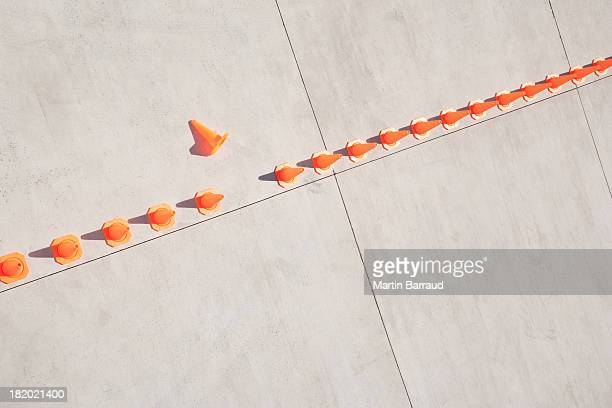 row of traffic cones with one on side - imperfection stock pictures, royalty-free photos & images