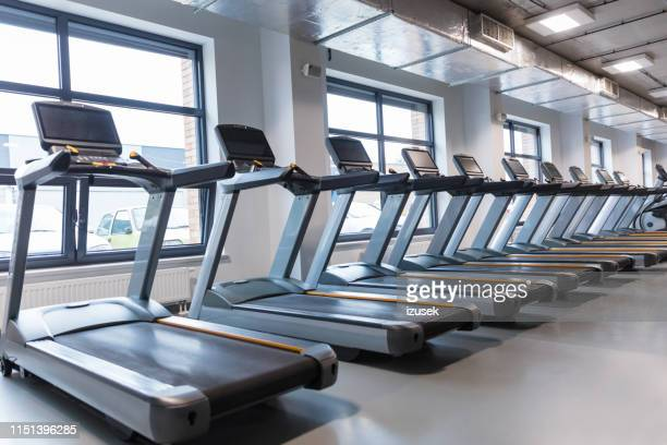 row of treadmills in a gym - leisure facilities stock pictures, royalty-free photos & images