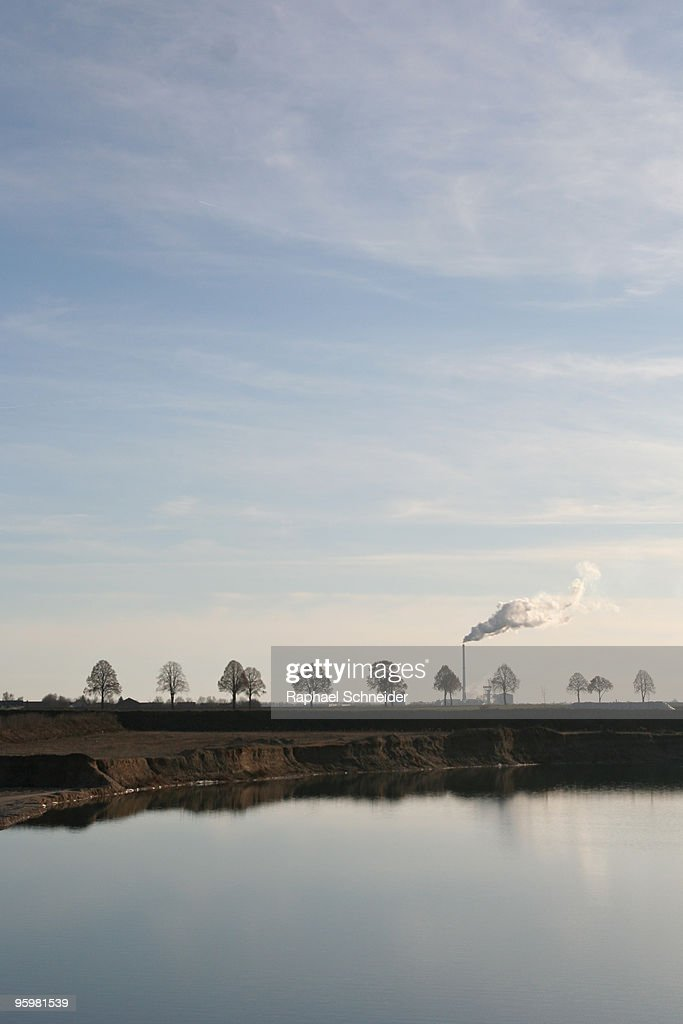 A row of trees with a smoke stack : Stock-Foto