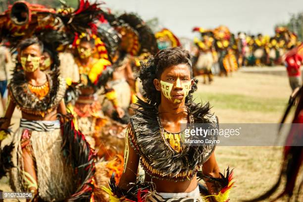 row of tribesman standing in line at festival - dinagyang festival stock photos and pictures