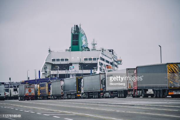 A row of trucks wait to board a ferry crossing the Irish Sea as a vessel operated by Irish Ferries Ltd sits docked at Holyhead Port operated by Stena...