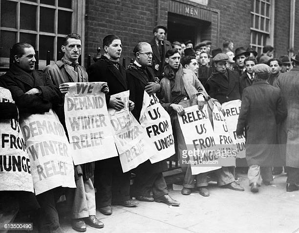 A row of unemployed men chain themselves along the railings outside a London Labour Exchange They hold posters that highlight the problems of poverty...
