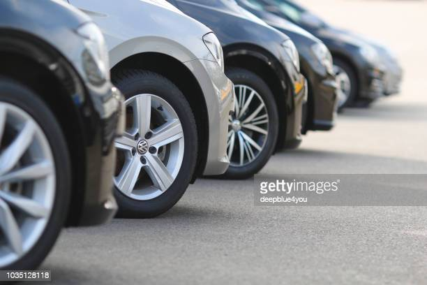 a row of used vw cars parked at a public car dealership in hamburg, germany. - showroom stock pictures, royalty-free photos & images