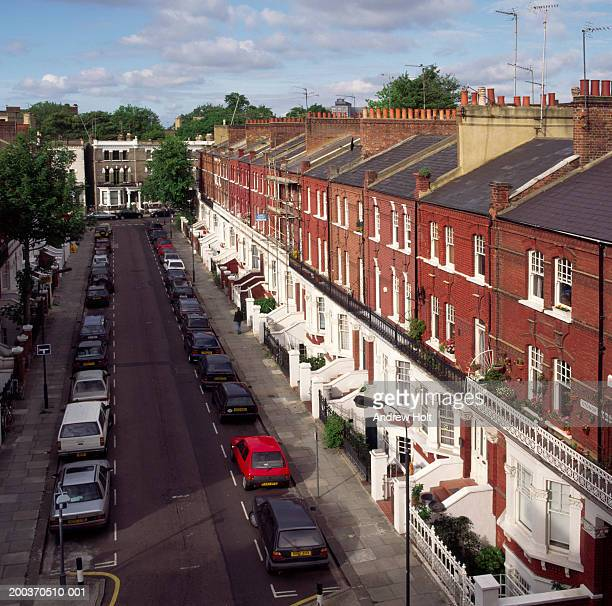 Row of Victorian terraced houses and cars parked in residential street