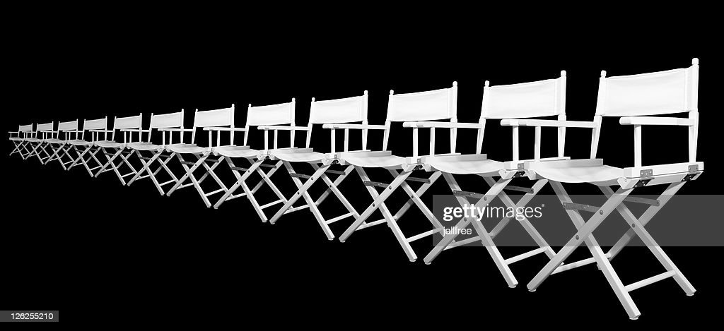 Row of white directors chairs on black background : Stock Photo