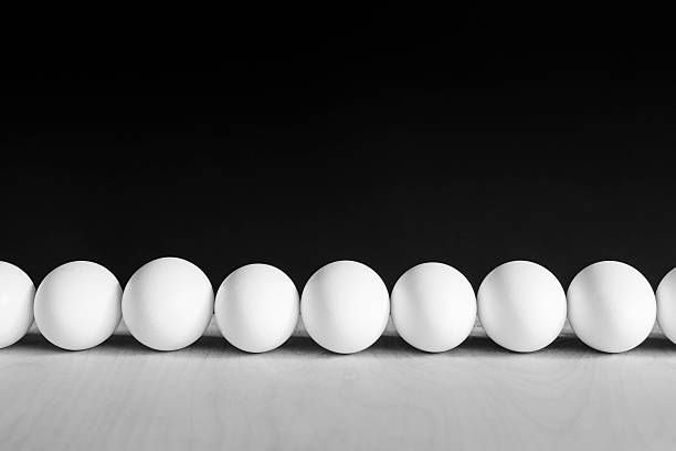 Row of white, free range, organic eggs, black background
