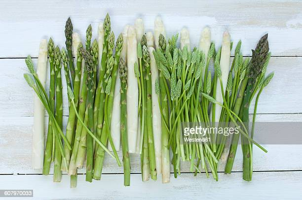 Row of white, green and wild asparagus on wood