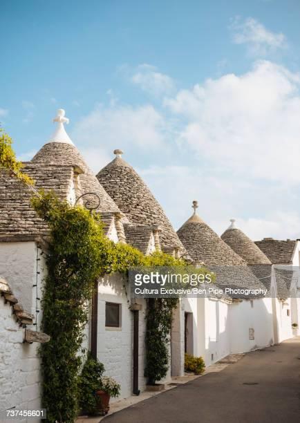 row of whitewashed trullo houses, alberobello, puglia, italy - alberobello foto e immagini stock