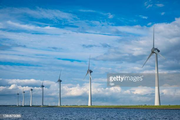 "row of wind turbines in a windpark during a windy day with clouds in the background - ""sjoerd van der wal"" or ""sjo"" stock pictures, royalty-free photos & images"