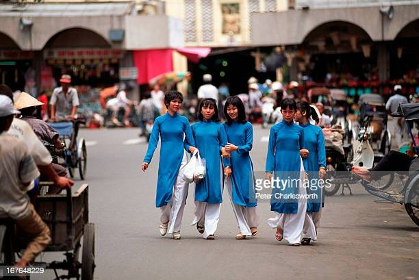 A row of women wearing identical national costumes called 'ao dai' walk on a central Saigon street