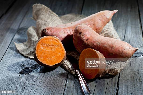 Row sweet potatoand knife on jute, wood