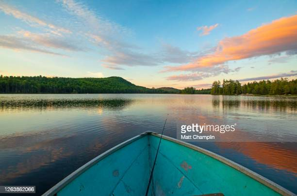 rowboat in lake at sunset - wilderness area stock pictures, royalty-free photos & images