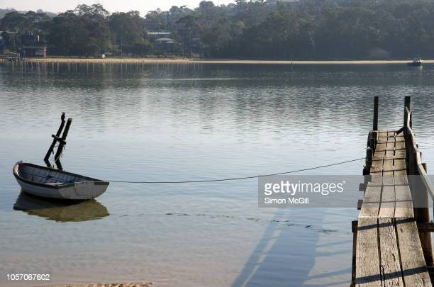rowboat moored at a makeshift wooden jetty on boggy creek, merimbula, new south wales, australia - makeshift stock pictures, royalty-free photos & images