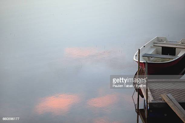 rowboat moored at calm lake during sunset - paulien tabak stock pictures, royalty-free photos & images