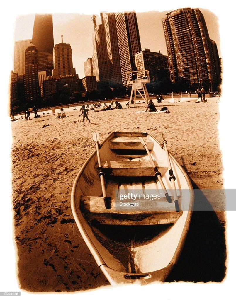 Rowboat stranded on beach, city behind : Stock Photo