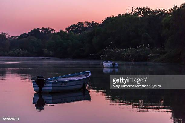 rowboats moored in calm lake by silhouette trees against orange sky - mary lake stock photos and pictures