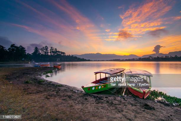 rowboats moored in lake against sky during sunset - tian abdul hanip stock photos and pictures