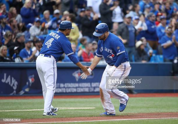 Rowdy Tellez of the Toronto Blue Jays is congratulated by third base coach Luis Rivera after hitting a tworun home run in the fourth inning during...