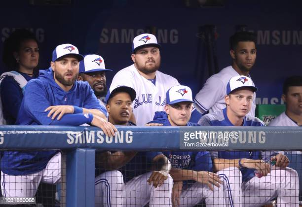 Rowdy Tellez of the Toronto Blue Jays looks on from the dugout alongside head athletic trainer Nikki Huffman and Kevin Pillar and Dwight Smith Jr #27...