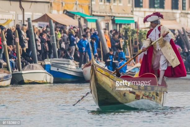 A rower dressing carnival costumes sails on Canaregio Canal at the end of the traditional regatta for the opening of the 2018 Venice Carnival on...