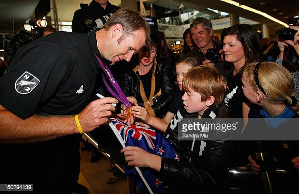 Rower Mahe Drysdale of the New Zealand Olympic team shows his gold medal to young fans at Auckland International Airport after competing in the 2012...
