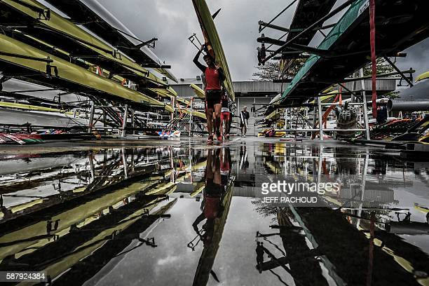 TOPSHOT Rowers carry their boats after a training session at the Lagoa stadium following the cancellation the day's races due to bad weather...