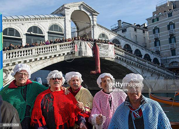 Rowers dressed in costume celebrate next to the Rialto Bridge at the end of the Befana Regatta on January 6 2014 in Venice Italy In Italian folklore...