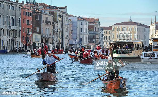 Rowers dressed in costume race along the Grand Canal for the Befana Regatta on January 6 2014 in Venice Italy In Italian folklore Befana is an old...