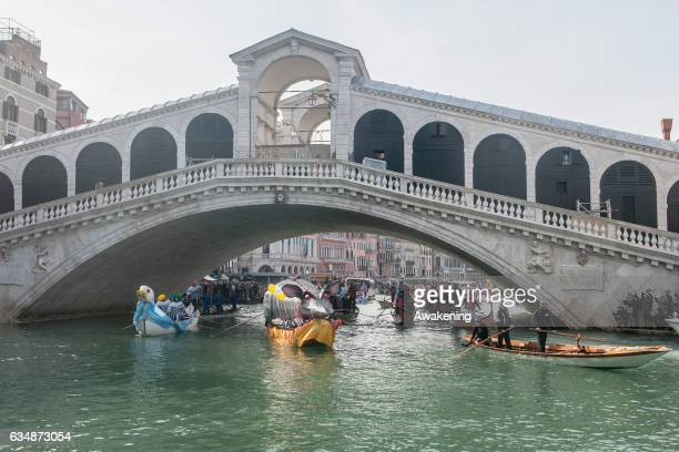 Rowers dressed with costumes sail under the Rialto Bridge at the traditional regatta on the Grand Canal on the opening day of the Venice Carnival on...