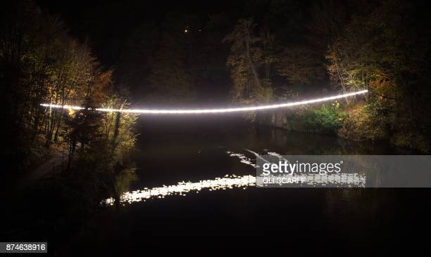 Rowers make their way beneath a light art installation entitled 'White Line' by artist Adam Frelin which features as part of Lumiere Durham light...