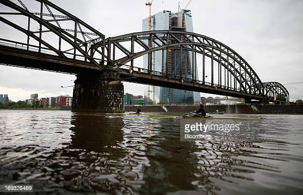 Rowers pass a bridge on the River Main in front of the European Central Bank's new headquarters still under construction in Frankfurt Germany on...