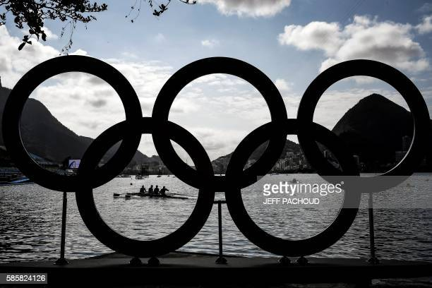 TOPSHOT Rowers practice in front of the Olympic Rings at the Lagoa Rodrigo de Freitas ahead of the Rio 2016 Olympic Games in Rio de Janeiro on August...