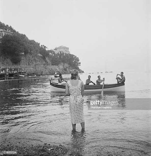 A rowing boat full of young men off Paraggi Beach near the tourist resort of Portofino Italy August 1952 Original Publication Picture Post 6023 unpub