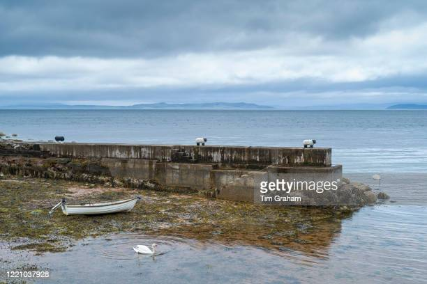 Rowing boat tied to a sheep bollard and moored on the seashore in dock near Corrie on the Isle of Arran Scotland