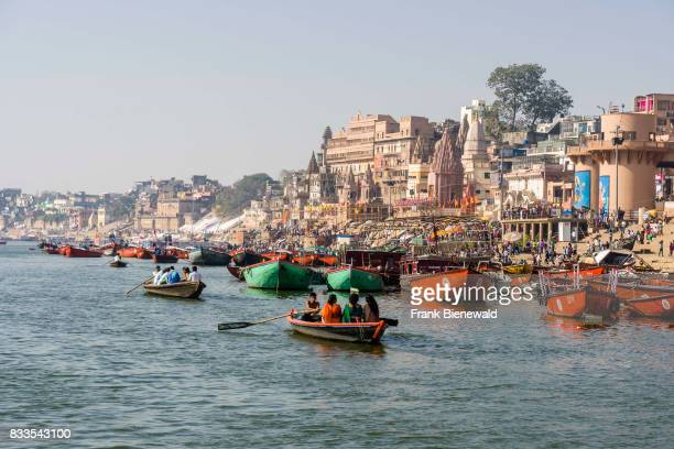 Rowing boats are driving on the holy river Ganges at Dashashwamedh Ghat Main Ghat in the suburb Godowlia