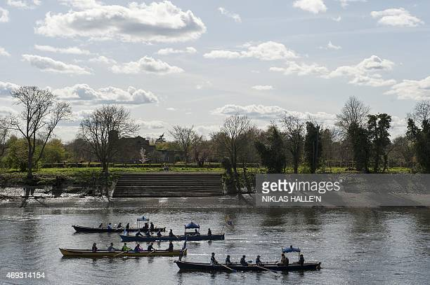 Rowing boats glide down the river Thames prior to the start of the boat race between Oxford university and Cambridge university on April 11 2015 in...